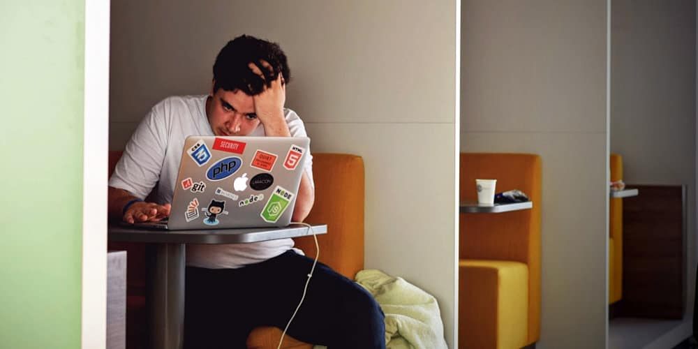 man frustrated laptop coffee shop