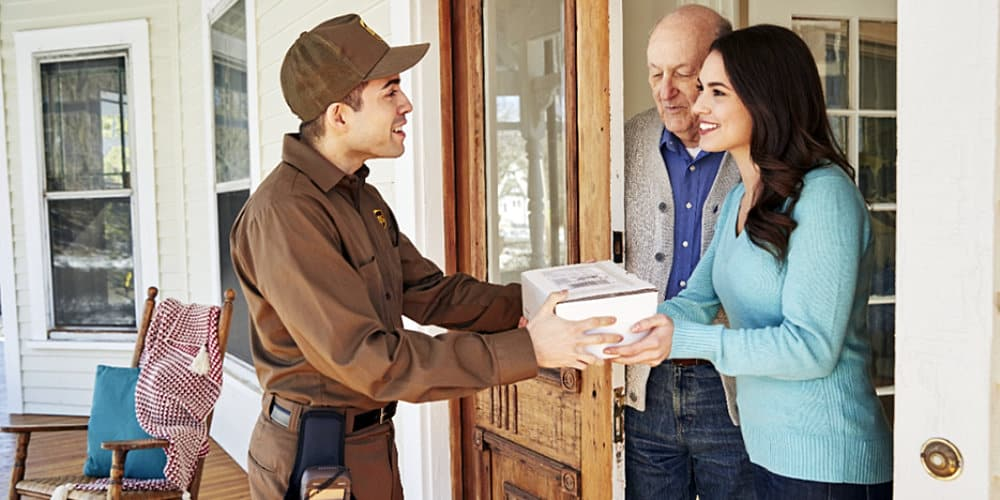 ups delivery man hands package couple
