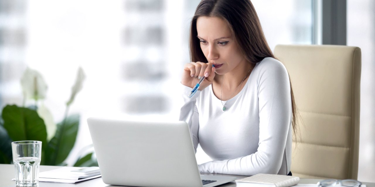 Business woman staring at laptop anxiously