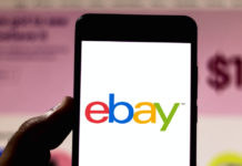 eBay logo on Smartphone with eBay Website on Desktop in Background