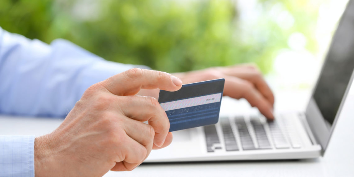 Man with laptop and credit card at table, closeup