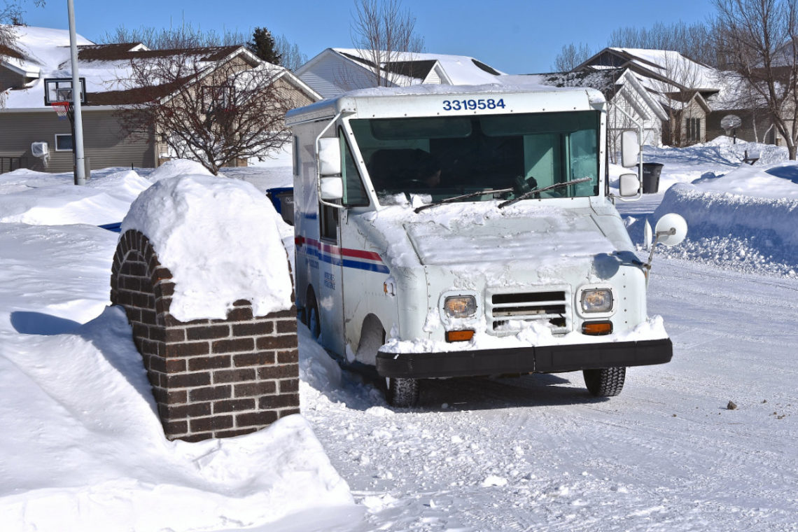 USPS delivery vehicle in a residential neighborhood during the winter season
