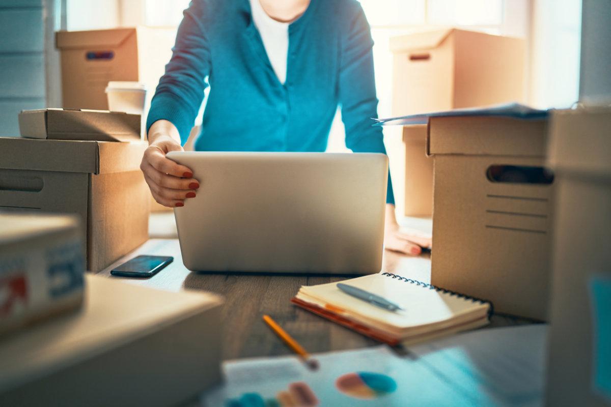 Woman entrepreneur using laptop to ship orders
