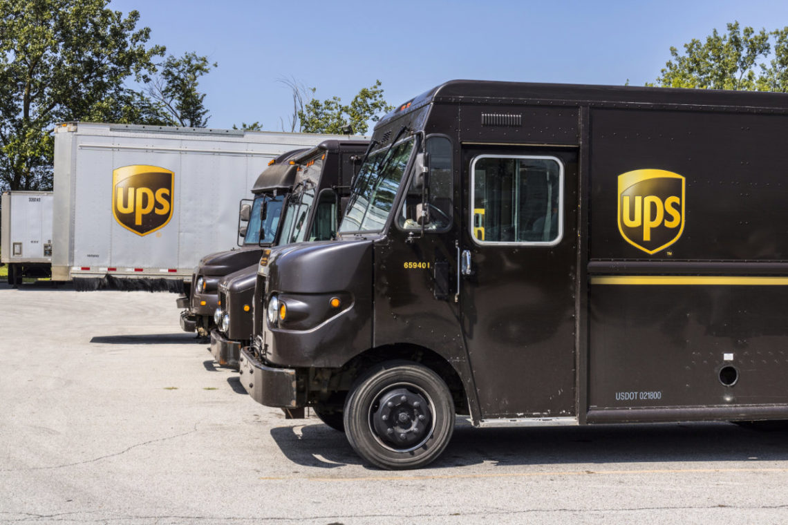 UPS trucks and trailers parked in logistics hub
