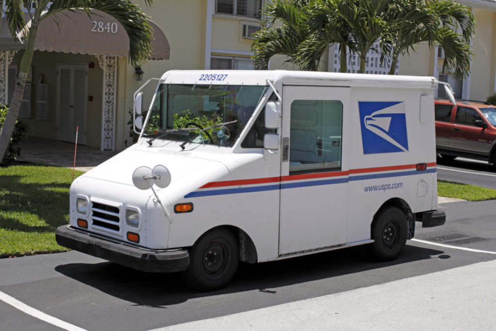 USPS delivery vehicle parked in neighborhood