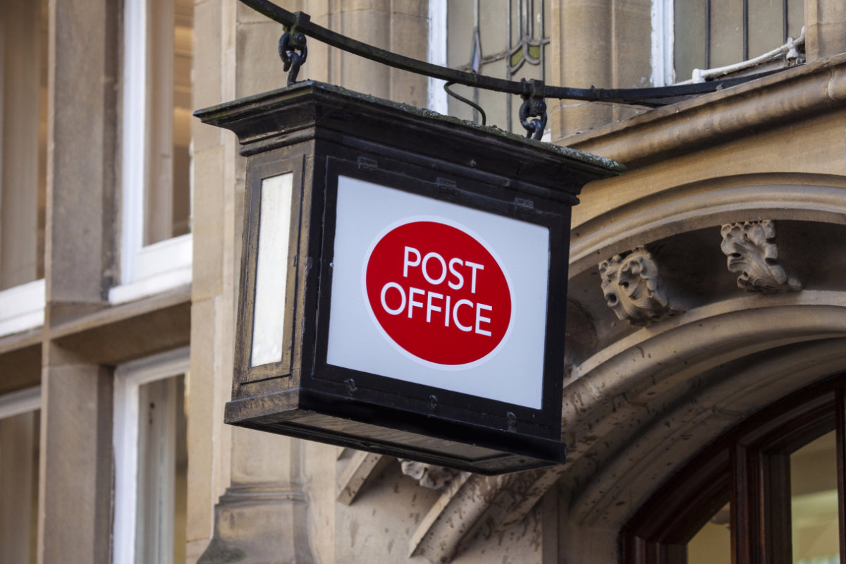 A Post Office sign hanging above a doorway.