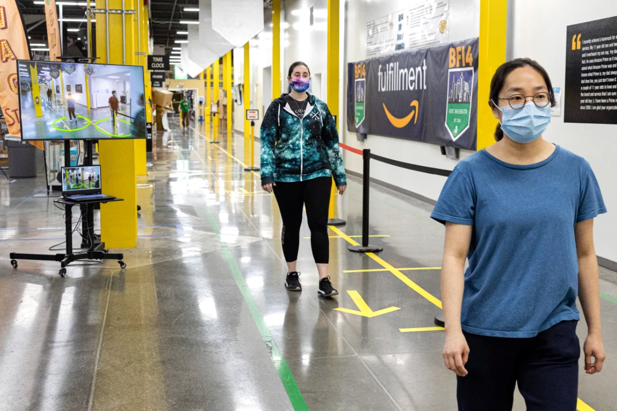 Amazon workers passing a health safety checkpoint in warehouse