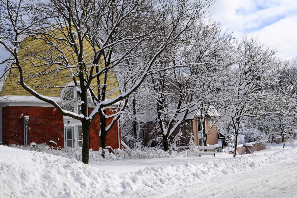 Winter street with lots of snow and colorful houses
